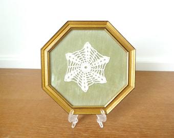 Framed crocheted star shaped doily with pale green velvet and gold octagonal frame