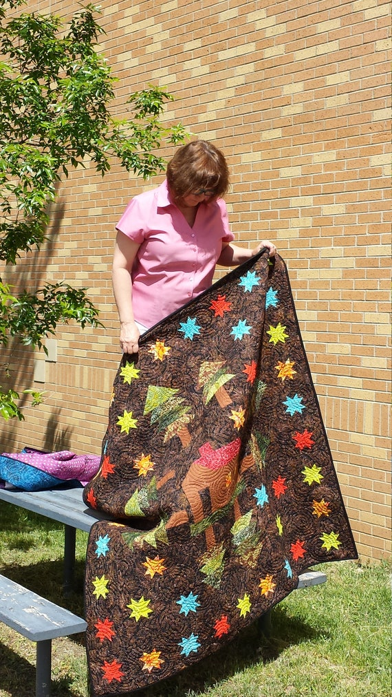 Cabin In The Woods Lap Size Quilt Kit in Batiks. Forest Pine Trees Surrounded By Sparkling Blue, Red, Yellow Stars. Rustic Wall Art