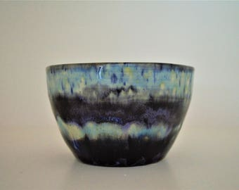 Small black, white and blue cup or bowl.