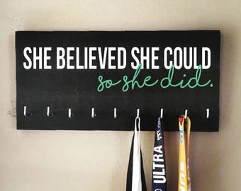 "Race Medal Holder - ""She believed she could SO SHE DID"" white and teal with black background"