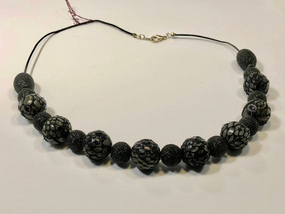 Handmade necklace with fabric sparkling and plaided black beads with black leather cord and silver plated endings and clasp