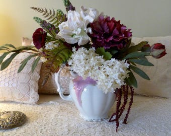 Cottage floral arrangement with lush color contrast in vintage ceramic  water pitcher.