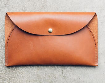 the west clutch in cognac // leather clutch with a single open pouch and snap closure