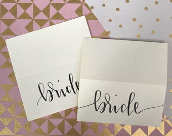 Cream hand lettered place cards for weddings and parties
