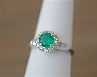 Emerald and diamond halo ring