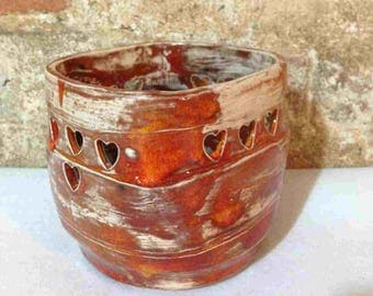 Rustic burnt orange coloured ceramic lidless jar with cutout hearts