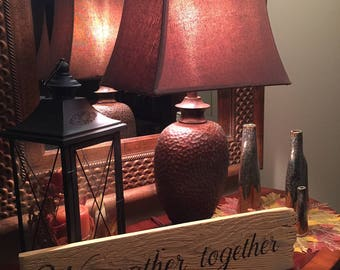 "Rustic distressed wooden ""We gather together"" sign"