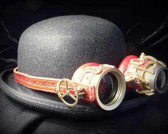 "Steampunk goggles in embossed red leather and brass with ""telescopic"" ocular, black lenses and folding gear"