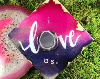 "Purple, pink and gold hand lettered ""i love us"" on canvas"