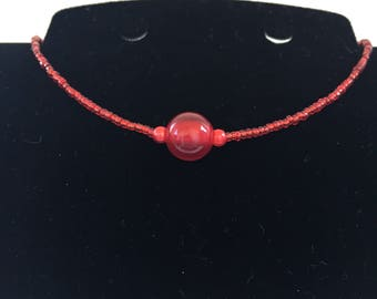 Elegant and simple red  bead short necklace, with large red feature bead.