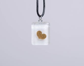 Heart from liquid gold sealed with white fused glass .