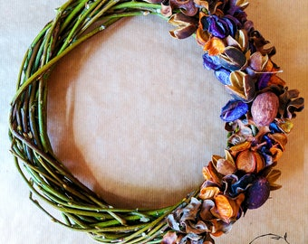 Wreath of woven branches decorated with dried nuts and flowers