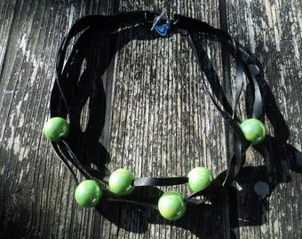 Necklace in inner tube recycled and iridescent green beads.
