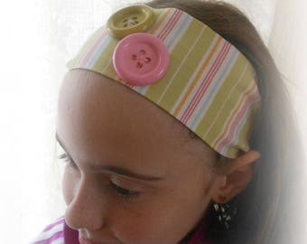 FABRIC HEADBAND HAS GREEN PLASTIC BUTTONS WITH STRIPES