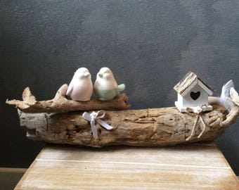Couple of birds on a branch of driftwood