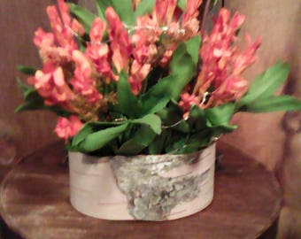 A small box wrapped in birch and filled with floral stems.