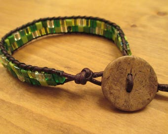Leather wrap bracelet with mixture of green, yellow, and clear glass beads with button closure