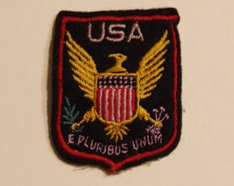 Embroidered with motto on the great seal of the United States. Emblem of the United States.