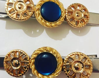Set of 2 hair clipswith blue and gold details.