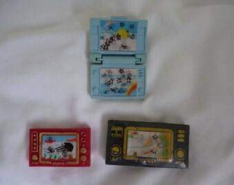 Three vintage novelty eraser game handheld game console