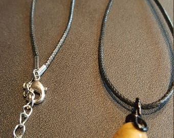 Tan stone pendant on a black cord necklace