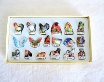 A vintage French set of feves, small ceramic tokens, statues, miniatures, Atlas Edition 1991, birds, butterflies, fish, cats, dogs