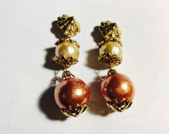 Fabulous large cream and dark taupe beads surrounded by gold tone findings clop on earrings.  Great vintage classics.