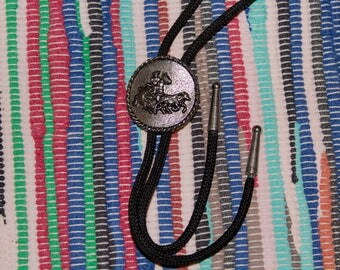 vintage bolo tie with metal emblem depicting a cowboy on horseback