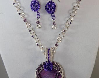 Purple gemstone with silver and purple wire wrapping.