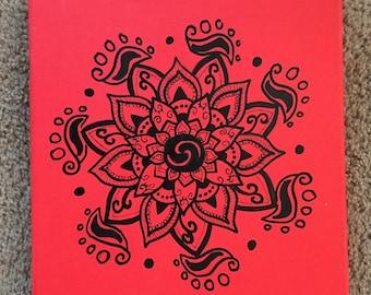 Mandala design on red canvas