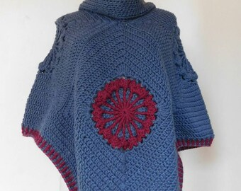 Gray, cowl neck, crochet poncho with maroon flower at font and back.