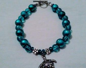 Sea Turtle dangling charm bracelet, hand beaded with Aqua glass beads, with a Toggle Clasp.