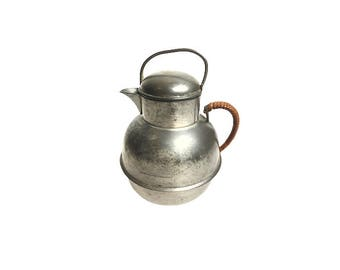"Vintage small pewter creamer with a removable lid and a rattan wrapped handle. The bottom is marked ""Marion Pewter 750""."
