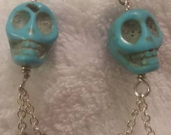 Turquoise skull drop earrings with black crystal dangles.