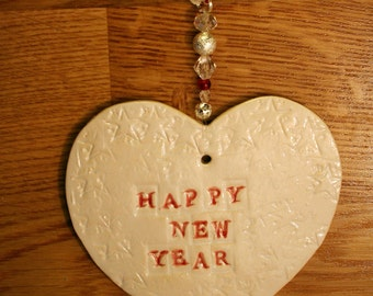 Happy New Year White Pottery Heart, a lovely gift in a white gossamer bag to celebrate the New Year handmade in my Sussex Pottery.