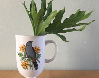 Sweet vintage white ceramic pedestal mug features Jay bird on green branch with orange flowers for tropical Old Florida home!