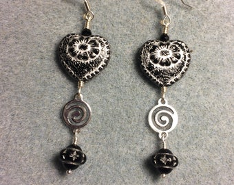 Black with silver inlay Czech glass heart bead dangle earrings adorned with silver swirly links and black Saturn beads.