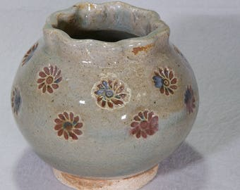 Small green globular ceramic pot with red iron oxide underglaze impressed daisies