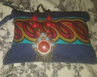 Jeans and ankara clutch with necklace.