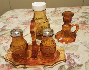 Amber glass salt and pepper shakers with a caddy, sugar dispenser and candle holder 6 piece set