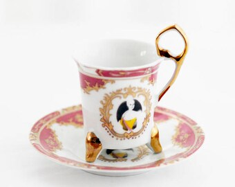 Delicate XS German cabinet-cup, goldcolor decorations on a pink and white porcelain base, featuring a Ladies' portrait.