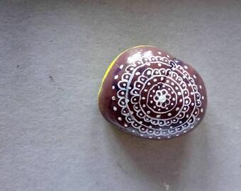 painted mandala stone has nails and permanent marker pen