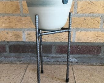 Colored clay Flowerpot on concrete iron holder legs