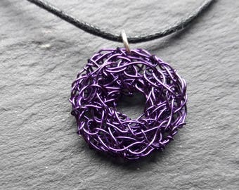 Purple wire circle necklace on black leather thong with silver coloured findings. Hand crocheted.