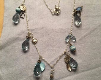 Necklace of Pale Blue Beads and Silver Charms, with Silver Chain.