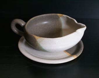 Grey and green gravy boat and saucer with raw unglazed areas