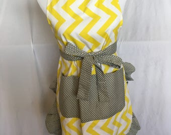 Women's apron with pocket. Yellow and white vertical chevron with gray and white polka dot pockets, straps, and pleats.