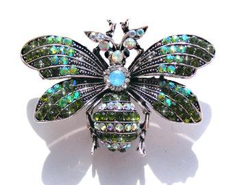 Broche papillon argenté, strass vert et AB multicolore.