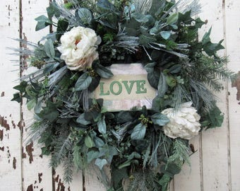Love is in the Air with this Ready to Ship Winter Wreath featuring Love Plaque in Center, Cream Frost Peony, Frosted Pine, Maidenhair Fern
