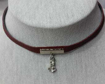 faux leather choker burgundy with a shiny silvr object with shiny stones.